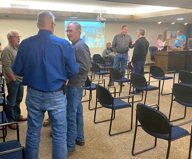 After Monday evening's special Ways and Means Committee at city hall, people linger to chat. Left to right on the left are CHEDA Board President Kurt Heldstab, CHEDA Board member Leon Kremeier, and former city council member Bobby Baird. Obscured in that group is Robin Brekken. In the background, Crookston Police Chief Paul Biermaier, seated, looks on while CHEDA Executive Director Craig Hoiseth talks with Jeff Fagerstrom of the Northwest Minnesota Housing Cooperative. In the far right background, CHEDA Board member Betty Arvidson talks with Ward 6 Council member Dylane Klatt.