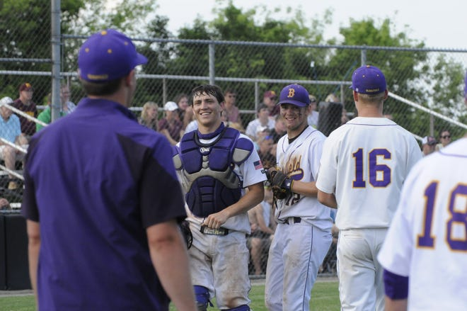 Blissfield's Gavin Ganun (center, right) and Zack Horky (center, left) smile after getting an out at home plate during the Division 3 regional semifinal game at Clinton against Manchester.