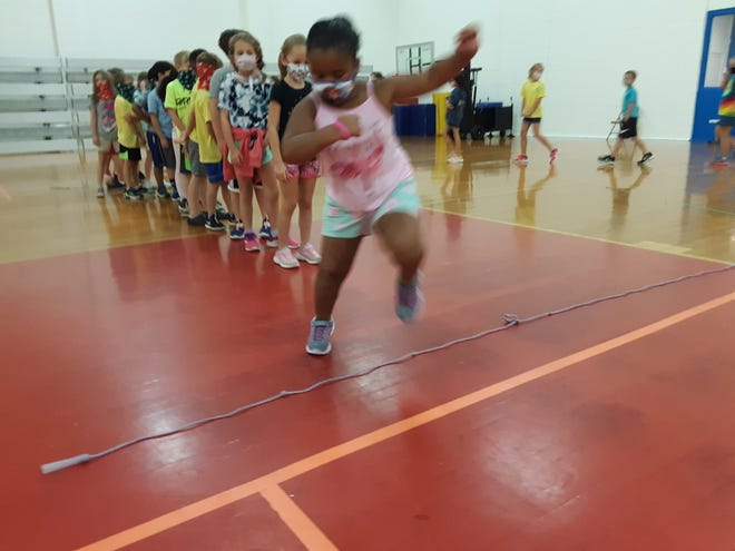 """Local kids play """"Jump the Creek"""", one of several activities at the YMCA Summer Camp."""