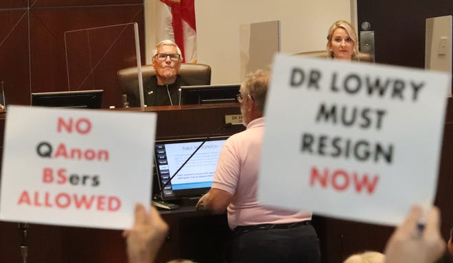 Volusia County Council member Dr. Fred Lowry, District 5, looks on as protesters hold signs demanding he resign, Tuesday June 22, 2021 during the council meeting in DeLand.