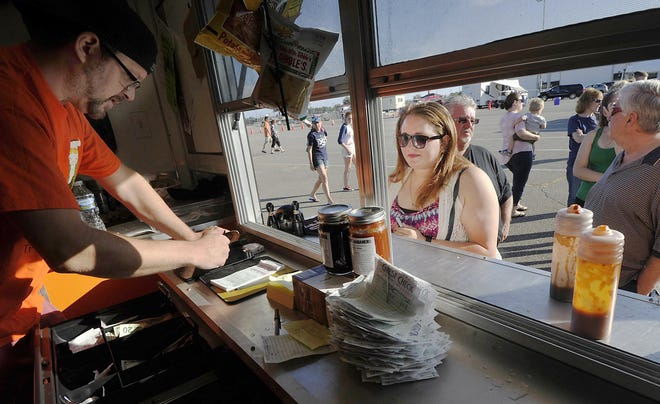 """Ray Smith, left, receives a message from Karissa Zelman at """"The governors stay"""" food truck at West Erie Plaza in Millcreek Township."""