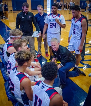 Truman head coach Rod Briggs (kneeling) talks with his team during a game in the 2019-20 season. Briggs is stepping down as a head coach for the Patriots to become an assistant principal and activities director at Pioneer Ridge Middle School.