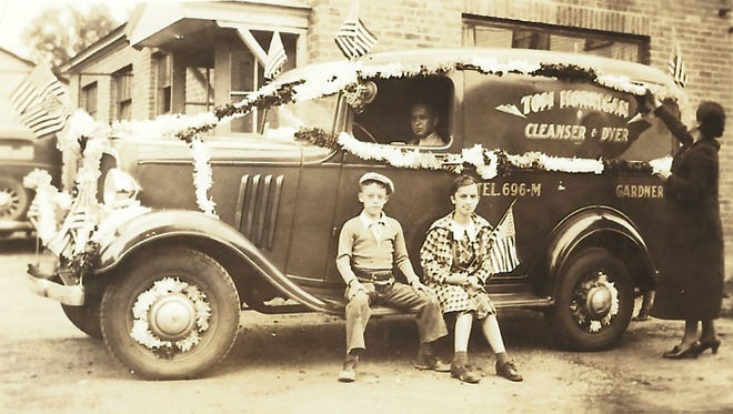 """Thomas J. """"Skip"""" Horrigan and his cousin, Claudia Brousseau, are shown sitting on the Horrigan Cleaners vehicle. Their uncle, Leo Brousseau, is the driver and his wife, Alma Brousseau, is decorating the car for the Gardner Memorial Day parade."""