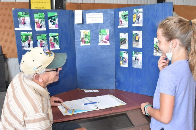 Keith Clement, left, of Woodhull learns from Hailey Olson about her tractor restoration project during 4-H general project judging on Saturday, June 19, in the merchants building on the fairgrounds in Cambridge. A member of Geneseo Jr. Leaders, Olson restored a John Deere 4020.