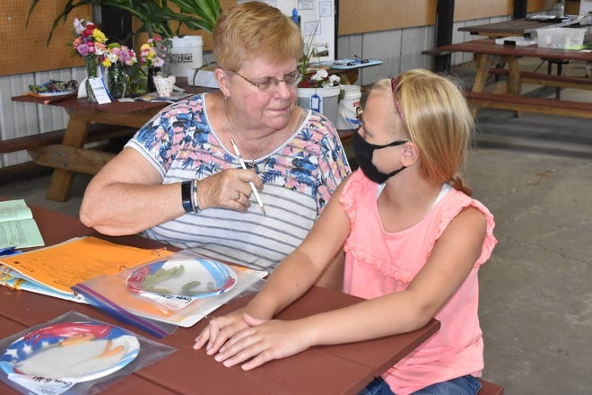 Linda Roehrs, left, of Cambridge volunteered to judge horticulture projects during 4-H general projects judging on Saturday morning, June 19, in the merchants building on the Henry County fairgrounds in Cambridge. She is shown talking with Gwen Gibbs of Western Jr. Farmers her veggie plate entry of snap peas and carrots.