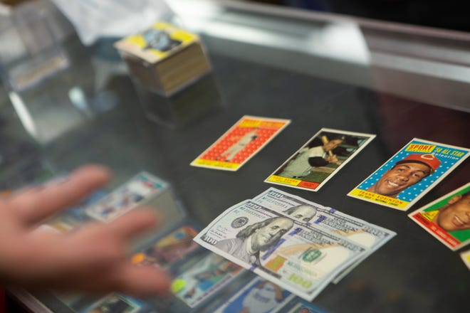 1,000,000 Baseball Cards owner Wally Militzer lays his offer of $200 on top of a display case for a selection of cards that customer Arthur Cassidy from Florissant brought in to sell in Ballwin, Missouri on Tuesday, June 15, 2021.
