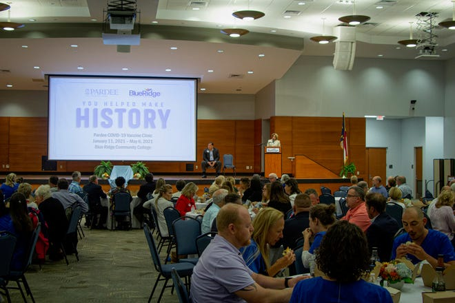 More than 200 people attend an event Tuesday to commemorate the first COVID-19 mass vaccination clinic in Henderson County.