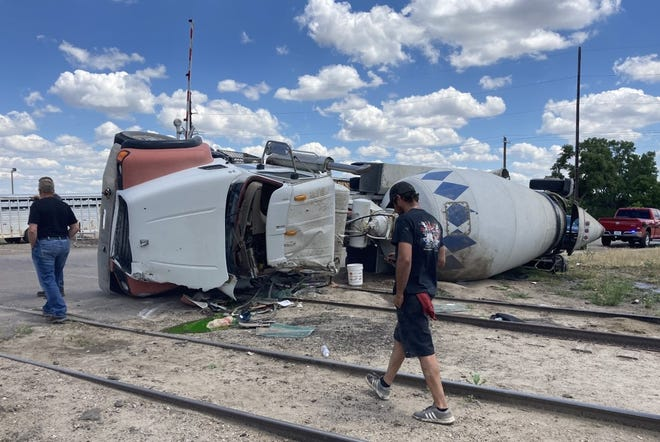 Several individuals walk past a cement truck that overturned near the Great Bend city limits Monday afternoon, injuring the driver. The rail line was closed until it could be inspected, according to the sheriff's office.