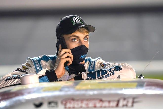 Carson Hocevar talks on his phone on pit road before the NASCAR 250 truck auto race at Daytona International Speedway, Friday, Feb. 12, 2021, in Daytona Beach, Fla. (AP Photo/John Raoux)