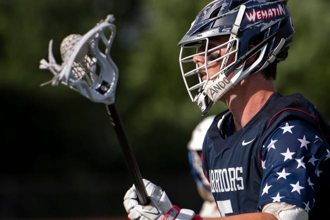 Lincoln-Sudbury senior Matt Dooley moves the ball up the field during the Division 1 North quarterfinals game in Acton, June 21, 2021. On his helmet is the last name of longtime L-S athletic trainer Yoshitaka Ando, who died from cancer in 2019.
