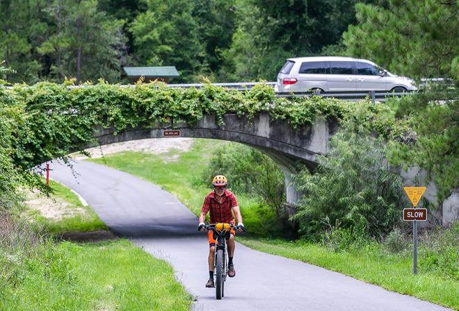 Bicyclist Jim Stansbury of Ocala makes his way up the steep incline at the SW 49th Avenue overpass on the Santos Trail on Tuesday. This part of the road is set for expansion as part of a larger project to improve/extend 49th Avenue between Marion Oaks and Ocala.