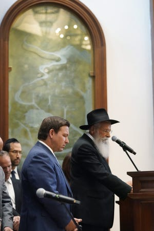 Florida Gov. Ron DeSantis, left, and Rabbi Sholom Lipskar participate in a moment of silence, Monday, June 14, 2021, at the Shul of Bal Harbour, a Jewish community center in Surfside, Fla. DeSantis visited the South Florida temple to denounce anti-Semitism and stand with Israel, while signing a bill into law that would require public schools in his state to set aside moments of silence for children to meditate or pray. (AP Photo/Wilfredo Lee)
