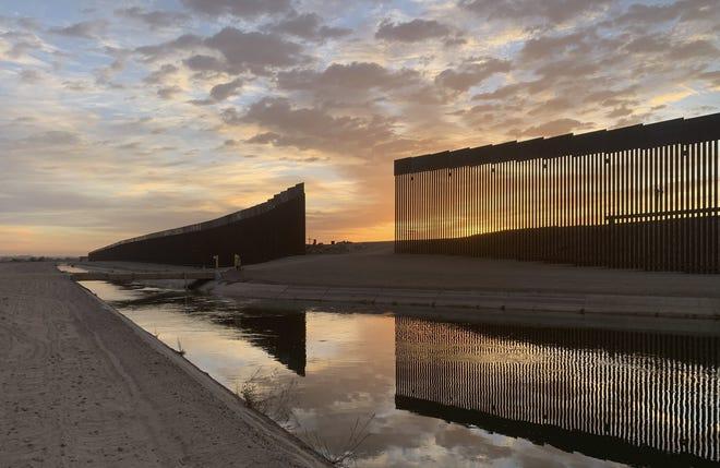 The sun sets above the U.S.-Mexico border wall, seen in Yuma, Ariz. (AP Photo/Eugene Garcia)