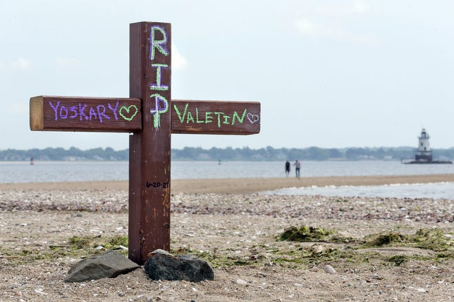 A cross on the Conimicut Point Park beach in Warwick is one of two memorials there honoring 10-year-old Yoskarly Martinez, of Providence, and Valentin Cardona Sanchez, 35, of Central Falls, who both drowned at the point on Sunday. Sanchez and two others tried to save Yoskarly as strong currents swept her away from the beach.