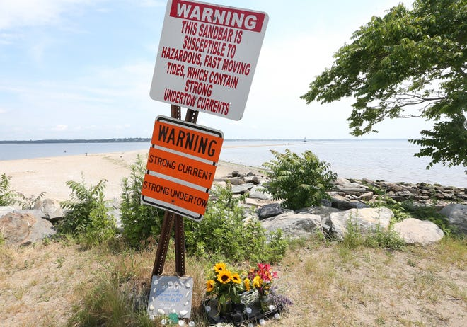 A sign warning of hazardous conditions at Conimicut Point stands above flowers and a plaque left in tribute to drowning victims Yoskarly Martinez and Valentine Cardona Sanchez.
