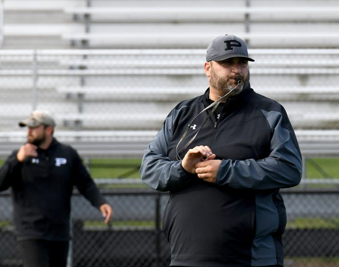 New Perry High School football coach Zach Slates works with players at the school.  Tuesday, June 22, 2021