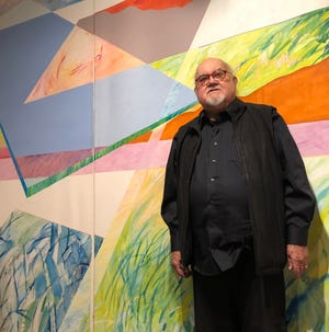 """Goshen artist Abner Hershberger stands in front of his 1987 painting, """"Agrarian,"""" now on display at the Midwestern Museum of American Art in Elkhart."""