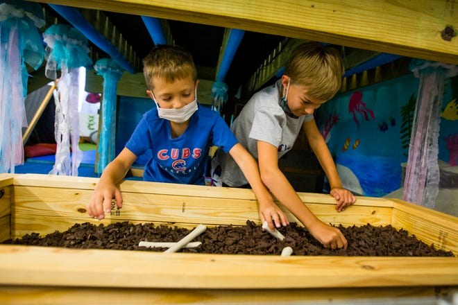 Teddy Shafer, 8, and Giovanni Lovisa, 8, play with a fossil digging exhibit June 22 at the Children's Museum of South Bend.