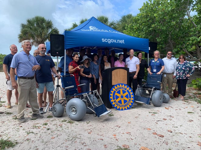 Members of the Rotary Club of Sarasota Sunrise and Sarasota County officials pose at Lido Beach with two new beach-accessible wheelchairs donated by the club to Sarasota County Parks, Recreation and Natural Resources during a celebration on June 22.