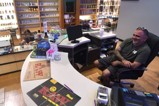 Owner Justin LaNasa sits behind the counter at Port City Vapor Kava & Oxygen Bar at Independence Mall in Wilmington, N.C., Tuesday, June 22, 2021. The store is one of the several new stores to open within the past year at the mall.   [MATT BORN/STARNEWS]