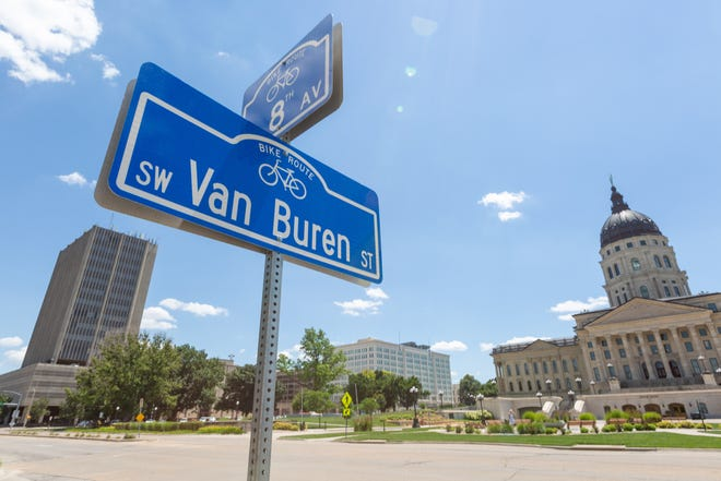 Blue signs indicating a bike route through Topeka are marked at S.W. Van Buren and 8th Ave. Topeka received $763,000 from the state for its 8th Avenue bike path expansion from Topeka Boulevard east to Madison Avenue.