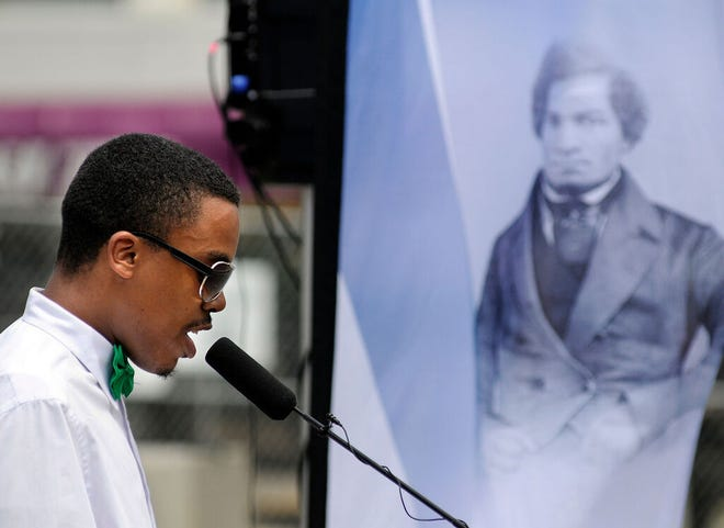 """Christian Wilson of Worcester reads a paragraph from """"What To The Slave Is The 4th Of July?"""" by Frederick Douglass on the Worcester Common Tuesday July 1, 2014. The event will be repeated this year on July 1."""