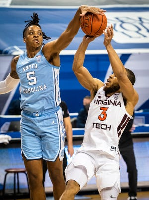 Armando Bacot of North Carolina stuffs a shot by Virginia Tech's Wabisaa Bede, right, in March at the ACC Tournament.