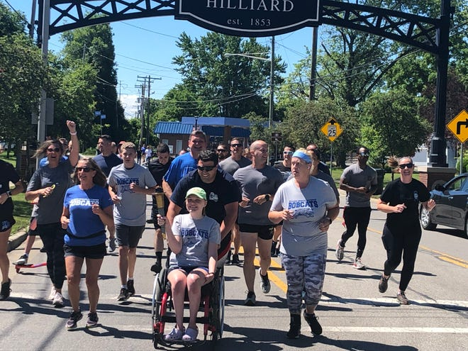 Riley Stang, 18, of Hilliard carries a torch on the final leg of the Hilliard Law Enforcement Torch Run for Special Olympics Ohio on June 22. Hilliard Division of Police Sgt. Tyler Harris is with Stang, a 2021 graduate of Hilliard Bradley High School and an athlete for the Hilliard Bobcats Special Olympics team.