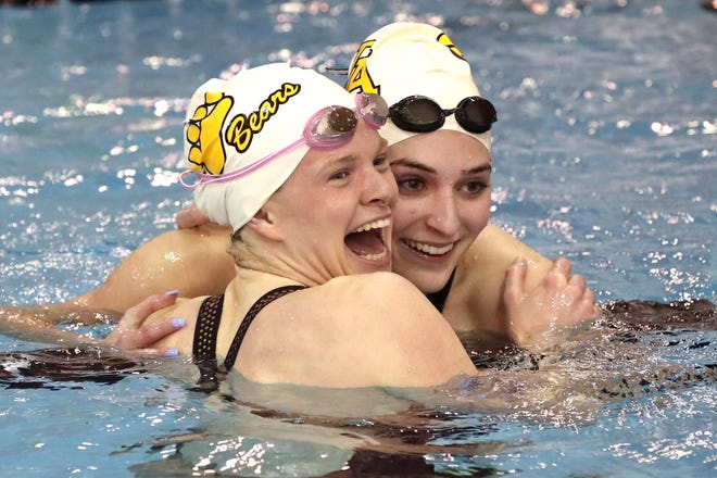 """Upper Arlington's Caroline Porterfield (left) and Riley Huddleston celebrate after tying for the Division I state title in the 50-yard freestyle Feb. 26 at Branin Natatorium in Canton. Despite challenges created by COVID-19, Porterfield said """"once you're in the water, all of that goes away."""""""