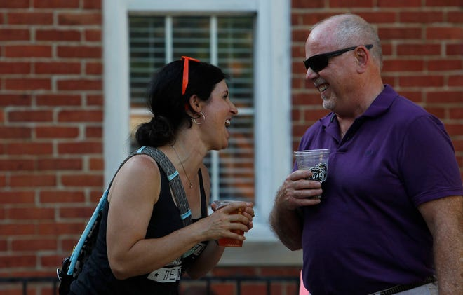 Marisa Akamine and Mark Johnston share a laugh during the first day of the Uptown Westerville Designated Outdoor Refreshment Area weekend June 17.