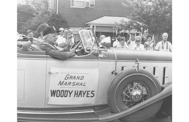 Ohio State University football coach Woody Hayes rides in a 1931 Cadillac with Len Immke while serving as the grand marshal for the Upper Arlington Fourth of July parade in 1985. Under Hayes, the Buckeyes won five national championships and 13 Big Ten titles. He and his wife, Anne, lived on Cardiff Road in Upper Arlington. Hayes died March 12, 1987.