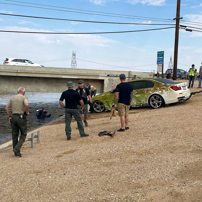 Sheriff's officials pull out a vehicle from the California Aqueduct near Highway 395 on Friday, June 18, 2021.