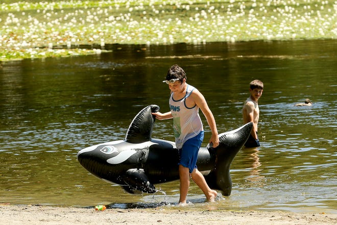 Victor-John Simard, 12, of Silverdale, hauls his inflatable orca out of the water after taking a swim at Island Lake Park on a warm Tuesday, June 22, 2021.