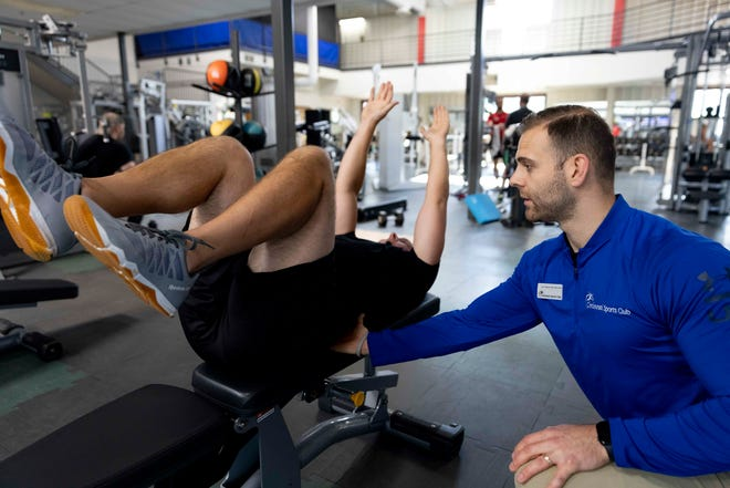 Vic Troha of Eden Park, a physical therapist and trainer at Cincinnati Sports Club, demonstrates an exercise with his client Kevin Moeller of Hyde Park on Tuesday, June 22, 2021, at the club in Fairfax.