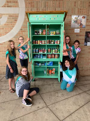 Members of Girl Scout Troop 40227 pose next to the repurposed armoire they transformed on June 18, 2021 at Imagination Station playground in Brighton.