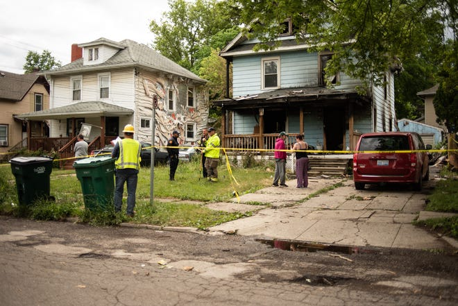 Fire officials and others outside of a home on Horton Street near Jerome Street in Lansing on Tuesday, June 22, 2021. Six people, including four children, were taken to a hospital after the home caught fire Tuesday morning.