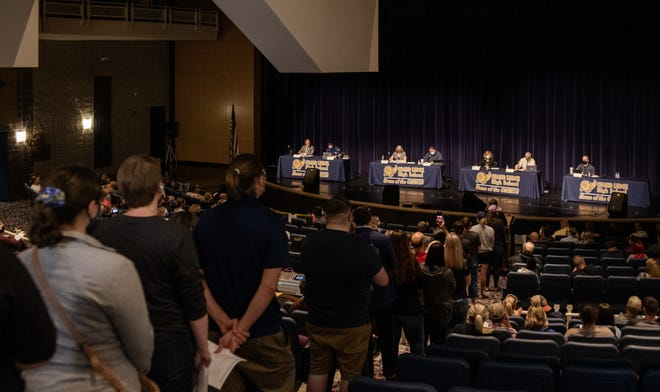 A line of people wait  to address the Grand Ledge School Board during the public commentary portion of the board meeting Monday, June 21, 2021, in the Grand Ledge High School auditorium.