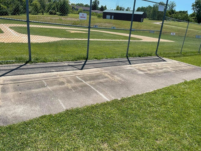 A vacant concrete pad remains along the first base line of the field where bleachers were stolen sometime late June 16 or early June 17.