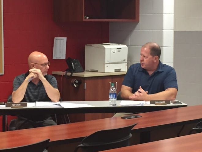 Assistant Superintendent Paul Walker, right, makes a point as Superintendent Tim Tarvin listens at Monday night's Shelby school board meeting.