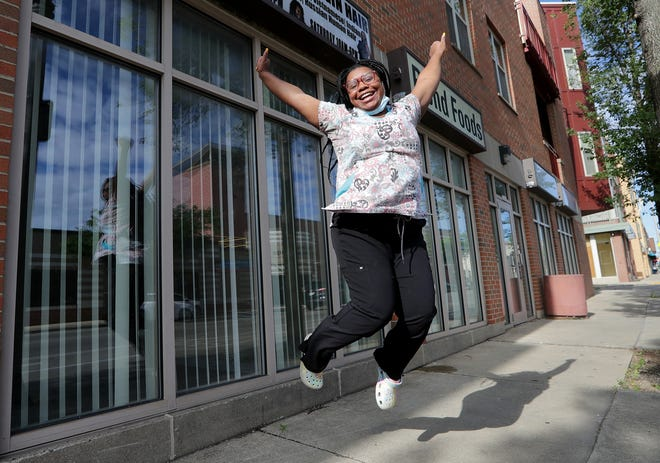 Kristina Rucker jumps for joy outside her new restaurant, Cloud 9 Cereal Bar, 3341 W. North Ave., in Milwaukee. Cloud 9 will feature dishes that incorporate cereal as well as traditional brunch options.