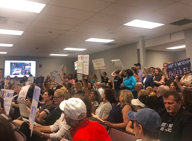 """Williamson parents and community members hold signs showing their opposition against English Language Arts curriculum """"Wit & Wisdom"""" and Superintendent Jason Golden's contract extension."""