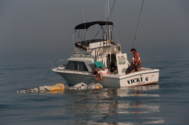 Eine Gruppe von Männern in einem privaten Boot versucht, ein scheinbar Rettungsfloß zu schleppen, das zwischen den Trümmern des TWA-Absturzes am Donnerstag, 18. Juli 1996, schwimmt. Viele Privatfahrzeuge halfen bei der Suche.  .