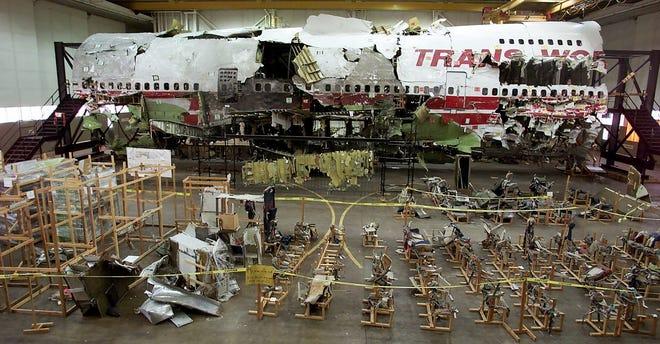 In diesem Aktenfoto vom 16. Juli 2001 befinden sich die Sitze, der Vordergrund und das Wrack von TWA-Flug 800 in einem Hangar in Calverton, New York.  Die Katastrophe vom 17. Juli 1996 war eine der berüchtigtsten Luftkatastrophen der Geschichte.  Einige diskutieren noch immer über die Feststellung, dass die Boeing 747 durch eine Explosion des zentralen Kraftstofftanks, die durch einen Funken aus einem Kurzschluss gezündet wurde, zum Absturz gebracht wurde;  eine Schlussfolgerung, die erreicht wurde, nachdem der zerfallene Jet wie ein Puzzle mühsam wieder zusammengesetzt wurde.