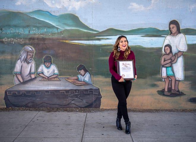 Gabriela Manzo sostiene su Premio a la Educación Cívica 2021 frente a un mural ubicado en la calle E. Alisal en Salinas, California, el lunes 21 de junio de 2021.