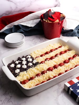 The flag is topped with grape tomatoes for the red stripes, shredded Monterey Jack cheese for the white strips, and crushed blue tortillas chips with sour cream for the stars