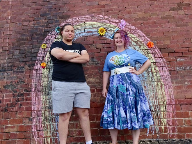 Kyle Johnson and Kristen Brown pose in front of a rainbow drawn outside of Brown's downtown studio for a Pride Month event on Saturday.