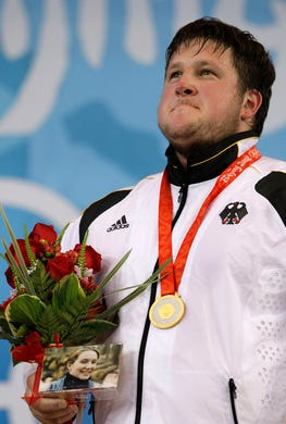 Gold medalist Matthias Steiner of Germany holds a picture of his late wife Susann, who died in a car accident in 2007, at the podium of the men's over 105 kg of the weightlifting competition at the Beijing 2008 Olympics in Beijing, Tuesday, Aug. 19, 2008.