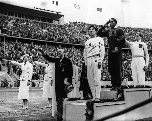 In this Aug.11,1936 file photo, long jump medalists salute during the medals ceremony at the Summer Olympics in Berlin. From left on podium are: bronze medalist Jajima of Japan, gold medalist Jesse Owens of the United States and silver medalist Lutz Long of Germany. Owens won four gold medals at the 1936 Berlin Games setting a world record in the 200 meters and helping the 4x100 meter relay to another record.