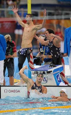 Michael Phelps, left, yells with Garrett Weber-Gale, right, as the USA team came from behind thanks to anchor swimmer Jason Lezak, in water, to win the gold during the men's 4x100 meter freestyle relay finals at the National Aquatic Center at the Beijing Olympic games. Lezak's legendary swim preserved Phelps' chance to win eight gold medals at the games.