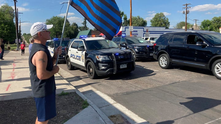 John Garrod, of Arvada, Colorado, stands as a line of about 30 police cars line up for a procession in honor of the officer who was fatally shot on Monday.